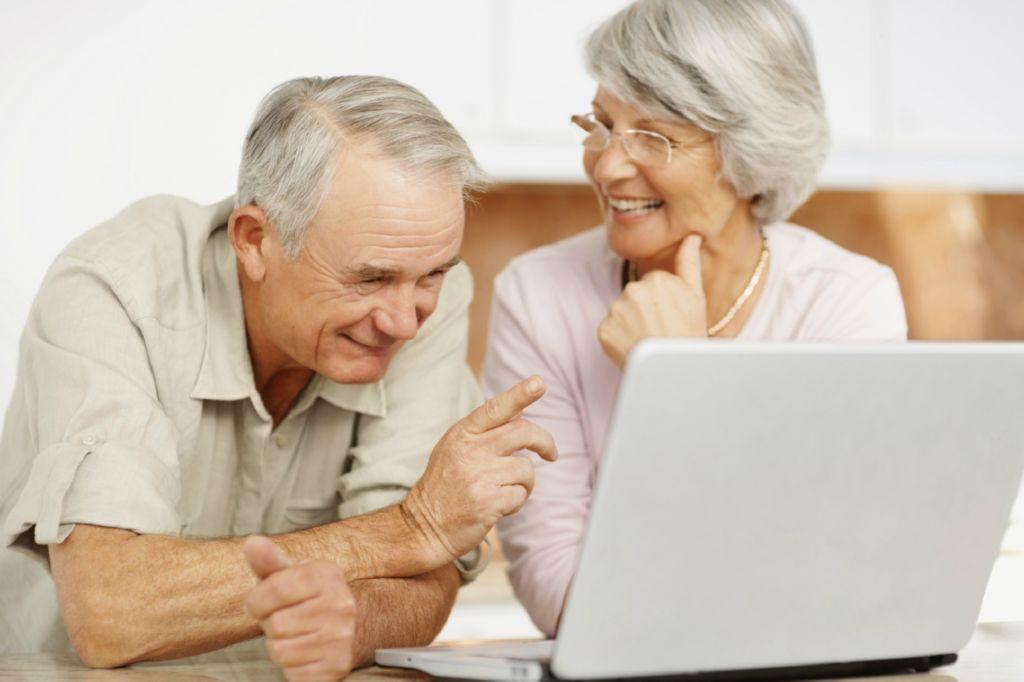 Dos personas ancianas riendo felices enfrente de un ordenador portatil