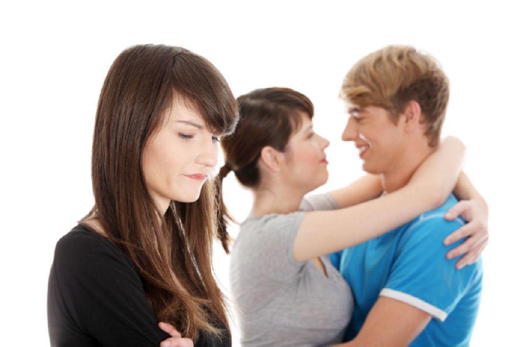 Mujer celosa de una pareja que se abraza y se mira enamorada