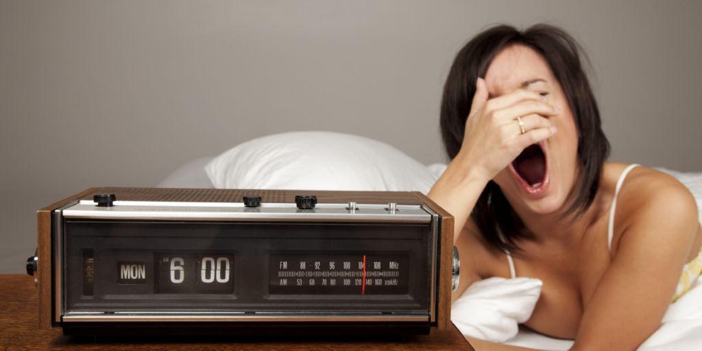 Mujer en la cama despertandose y bostezando y un despertador antiguo con radio a su lado