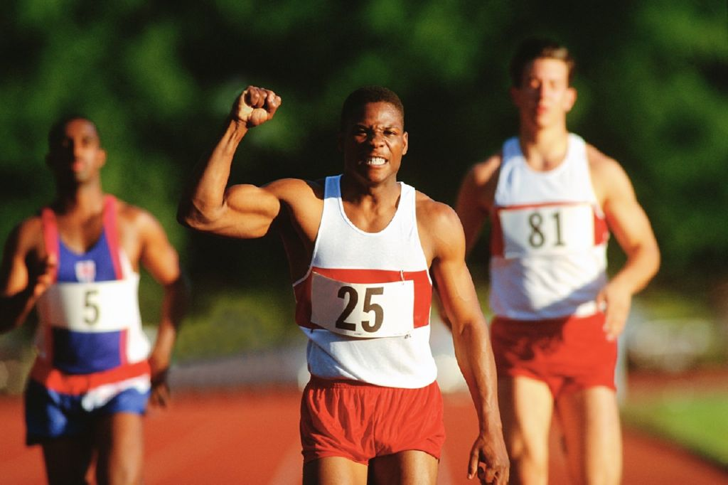 Un corredor de atletismo levantando su puno al llegar a la meta y dos corredores mas detras de el
