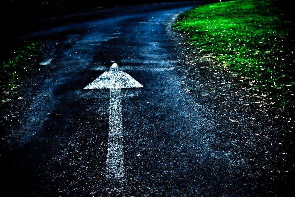 Una flecha pintada en un camino de noche